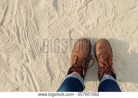 View From Above To A Pair Of Hiking Trendy Brown Boots With Shoelaces On Sandy Gritty Background. Te