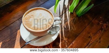 A Hot Cup Of Cappuccino Coffee With Milk Foam On A Wooden Table Under The Light Of The Morning Sun,