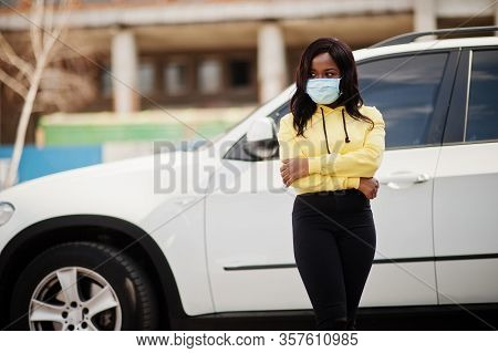 African American Young Volunteer Woman Wearing Face Mask Outdoors Against Suv Car. Coronavirus Quara