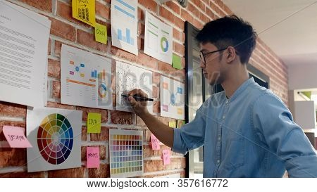 Design And Think, Young Asian Creative Design Man Thinking While Writting Plan On Paper Work Ideas A