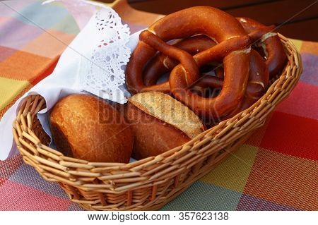 Close Up Several Traditional German Pretzel Bread Knots And Fresh Buns In Bread Basket On Table, Hig