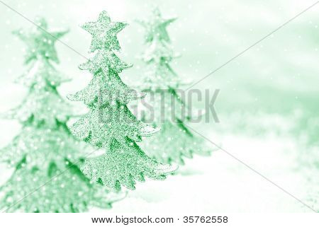 Shiny miniature tree ornaments on silver background with snow. High key, green toned macro with extremely shallow dof.  Selective focus on second tree.  Copy space included.