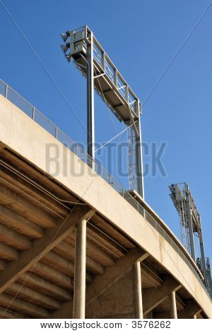 Banks of floodlights supported on steel frames college football stadium poster
