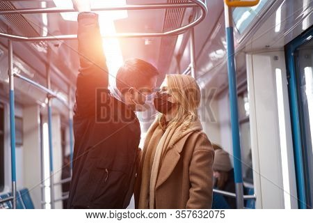 Young Couple In Medical Masks Holding Handrails In Subway Car. Coronavirus Pandemic. Lensflare Effec