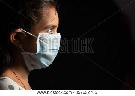 Young Teenager Girl With Medical Face Mask In Dark Room At Home Quarantine Due To Covid 19 Or Corona