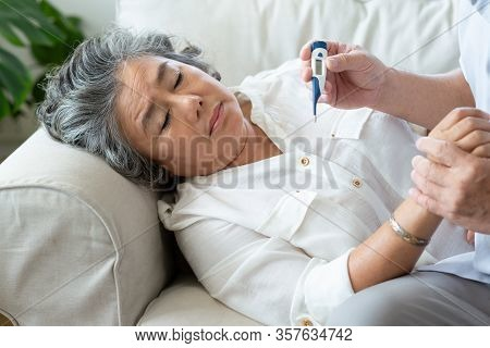 Elderly Woman Having Cold During Lie Down On Couch While Senior Man Checking Temperature Of His Wife