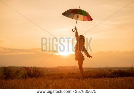 Side View Of Carefree Young Female In Trendy Mini Dress Holding Colorful Umbrella, Standing In Field
