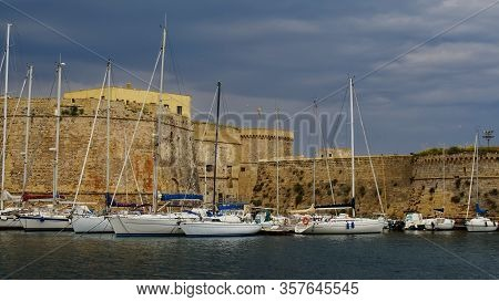 White Yachts Against The Background Of The Medieval Walls Of The Old Italian Fortress.