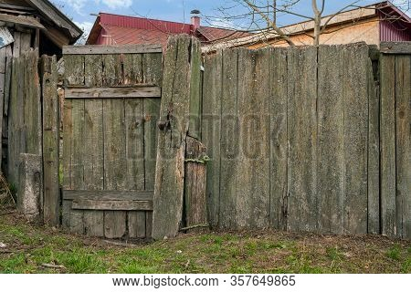 Rural Scene. Run-down Wooden Fence With Wicket For Entrance In Yard Of Rural House. From Weathered O