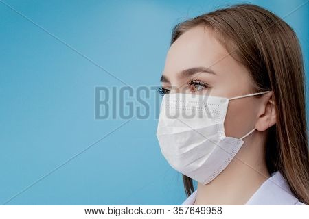 Doctor Nurse Smiling Behind Surgeon Mask. Closeup Portrait Of Young Caucasian Woman Model On Blue Ba