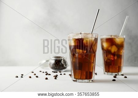 Two Glasses Of Iced Coffee And Metal Straws On A Concrete Table. Iced Coffee On A Light Background.