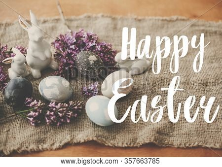 Happy Easter Text. Easter Greetings Card. Modern Easter Eggs, White Bunnies And Lilac Flowers On Lin
