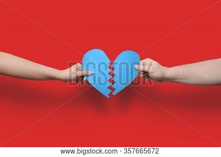 Two Arms Reaching From The Sides Holding A Blue Paper Cut Out Broken Heart. This Image Could Illustr