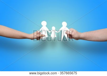 Two Arms Reaching From The Sides Holding A Paper Cutout Nuclear Family. This Image Could Illustrate