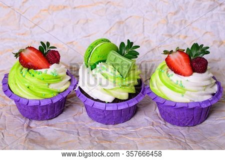 Three Cupcakes With Whipped Cream, Chocolate Bar, Strawberry , Decorated Macaroons On Crumpled Paper