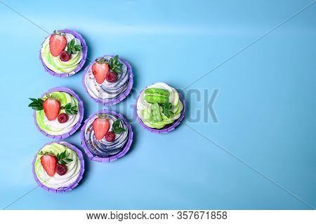 Cupcakes With Whipped Cream Decorated Chocolate Bar, Strawberry , Macaroons On Blue Background. Pict