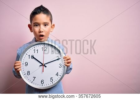Young little boy kid holding big minute clock over isolated pink background scared in shock with a surprise face, afraid and excited with fear expression