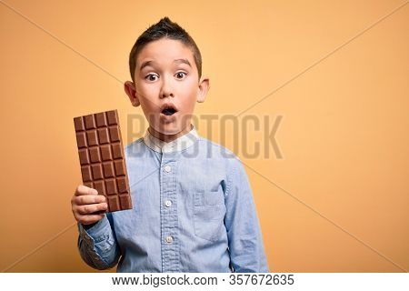 Young little boy kid eating sweet chocolate bar for dessert over isolated yellow background scared in shock with a surprise face, afraid and excited with fear expression