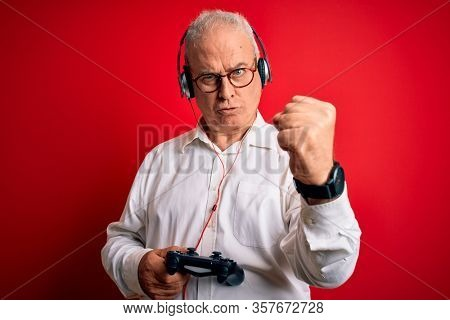 Middle age handsome hoary gamer man playing video game using joystick and headphones annoyed and frustrated shouting with anger, crazy and yelling with raised hand, anger concept