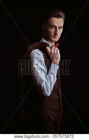 Portrait of a handsome man in elegant classic suit and bow tie on a black background. Business style. Men's fashion.