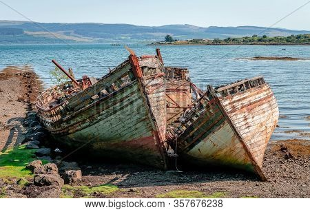 Beautiful Seascape With Three Semi-destroyed Old Fishing Boat In The Beach And The Sound Of Mull In
