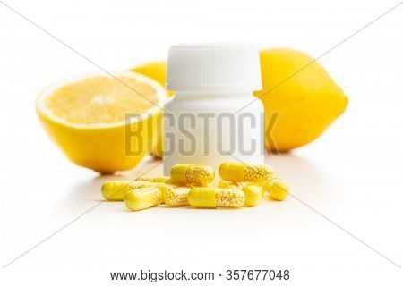 Vitamin capsules. Vitamin C pills with pill bottle and lemon fruit isolated on white background.