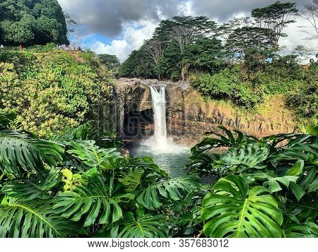 Rainbow Falls Is A 80ft. Tall Waterfall On The Big Island Of Hawai'i Surrounded By The Lush, Green,