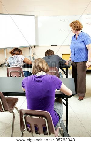Students taking a standardized test as a teacher looks on to ensure no cheating.