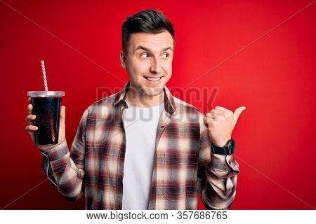 Young handsome caucasian man drinking a fresh soda refreshment over red background pointing and showing with thumb up to the side with happy face smiling