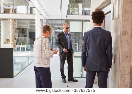 Business people and a blind man with a cane wait for the elevator