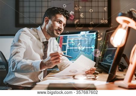 Happy Bi-racial Trader Holding Paper Near Computer With Graphs, Dollar And Euro Signs