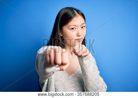 Young beautiful asian woman wearing casual sweater standing over blue isolated background Punching fist to fight, aggressive and angry attack, threat and violence