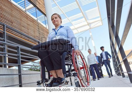 Disabled businesswoman in a wheelchair on a ramp to the office for inclusion
