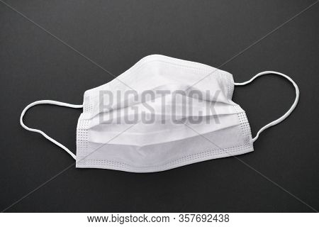 White Mask With Rubber Ear Straps On Dark Background. Typical 3-ply Surgical Mask To Cover The Mouth