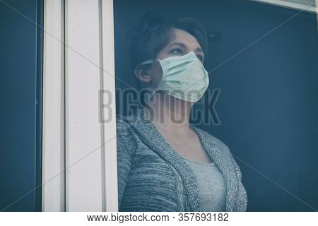 Woman wearing a protective face mask and looking out the window of her home because of an epidemic of corona virus covid-19. Home quarantine and self isolation concept