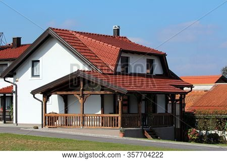 New Small Suburban Family House With Front Wooden Porch And Brand New Roof Tiles Surrounded With Pav