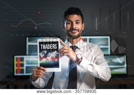 Happy Bi-racial Man Holding Digital Tablet With Traders Letters