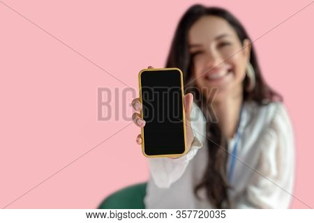 Young Pretty Dark-haired Woman Showing Her Smartphone