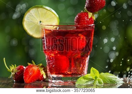 Refreshing Red Strawberry Drink In A Glass, With The Addition Of Lime, Mint And Ice Cubes, Next To I