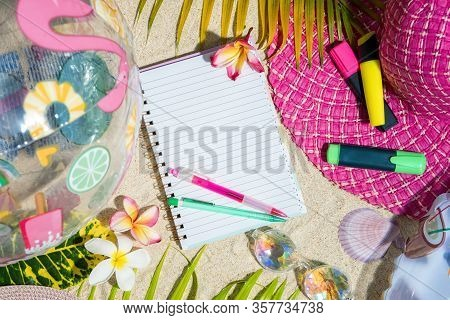 Blank Writing Note Pad With Pink And Green Pen On Sand, Surrounded By Green Palm Leafs, Sea Shelles,