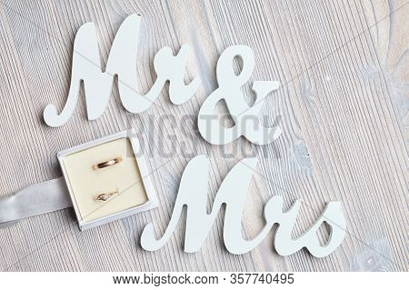 Wedding Rings In A Box Next To The Inscriptions Mr And Mrs On A Wooden Background. Close Up.