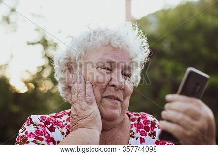 Portrait Of Mature Woman Talking On Smartphone Outdoor. Senior Woman Smiling And Talking On The Phon