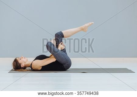 Relaxing Back Pain Exercise Concept. Attractive Sportive Woman Doing Pilates Exercise Lying On Yoga