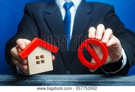 A Man Holds A House And The Red Prohibition Symbol No. Bank Refuses To Provide A Mortgage Loan. Hous