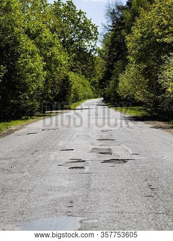 Old Paved Leaky Road In The Forest, Poor Quality And Without Repair