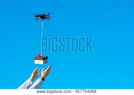 Multicopter Drone Flying With A Gift Box Isolated On A Blue Sky, Concept Of Modern Fast Delivery Met
