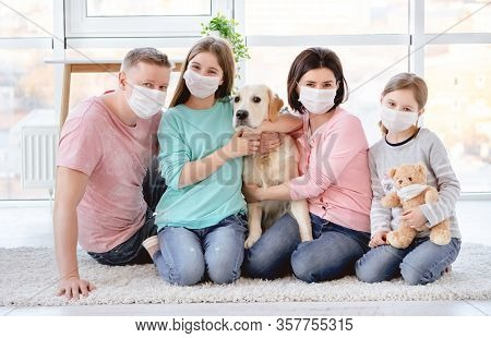 Beautiful family in medical masks against coronavirus at home
