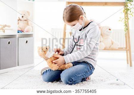 Lovely little girl listening teddy bear by phonendoscope