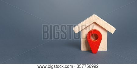 Figurine Wooden House And Red Location Pointer. The Concept Of The Location Of A Building, Surroundi