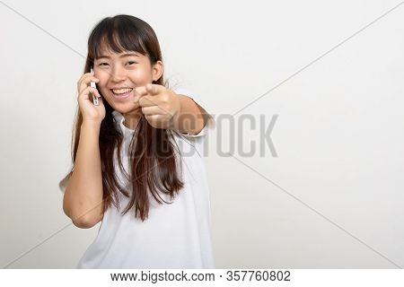 Portrait Of Happy Young Asian Woman Talking On The Phone And Pointing At Camera
